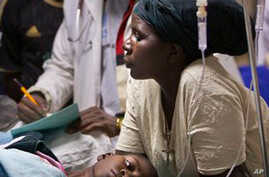 A woman cradles the head of a young patient injured in a g