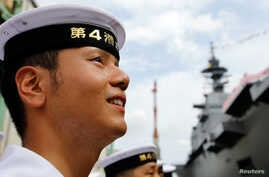 A member of Japan's Maritime Self-Defense Force looks at its new helicopter destroyer DDH183 Izumo, the largest surface combatants of the Japanese navy, before its launching ceremony in Yokohama, south of Tokyo August 6, 2013.