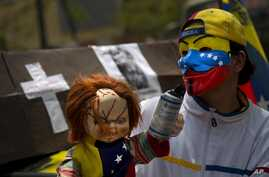 A protester with a Guy Fawkes mask, painted with the Venezuelan flag colors, carries a doll with a tear gas canister during a march in Caracas April 15, 2014.