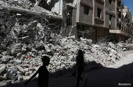 Children walk past the rubble of damaged buildings at Ain Tarma, and eastern Damascus suburb of Ghouta, Syria,  July 19, 2017.