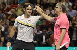 Roger Federer, of Switzerland, left, celebrates with partner Bill Gates as they play an exhibition tennis match against Jack Sock and Savannah Guthrie in San Jose, Calif., Monday, March 5, 2018.