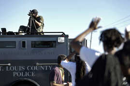 A member of the St. Louis County Police Department points his weapon in the direction of a group of protesters in Ferguson, Missouri, Aug. 13, 2014.
