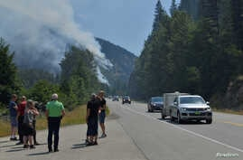 Tourists from Denmark stop to photograph one of several wildifres burning near Little Fort, British Columbia, Canada, July 9, 2017.