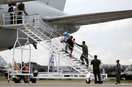 Venezuelan descend from a Brazilian Air Force plane after arriving at the Eduardo Gomes International Airport in Manaus, Brazil, May 4, 2018.
