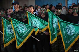 FILE - Palestinian youths hold Hamas movement flags during a rally near the Rafah border between southern Gaza Strip and Egypt on February 5, 2015 to condemn the decision of an Egyptian court to ban the armed wing of Palestinian Islamist movement.