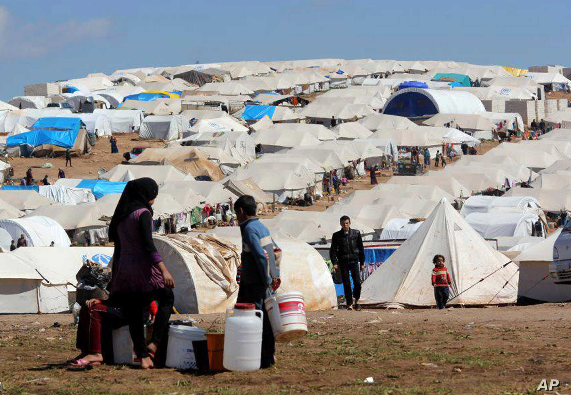 Syrian refugees filling their buckets at Atmeh refugee camp, in the northern Syrian province of Idlib, Syria, Apr. 5, 2013