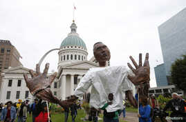 Marchers carry a papier-mache representation of slain Michael Brown, with his hands up, during rallies in Missouri, Oct. 11, 2014.