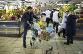 FILE - A man pushes a cart with food items at a grocery store in Moscow, Russia, April 2, 2015.