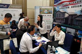 Chinese visitors seek information of the U.S. government's EB-5 visa program at the exhibitor booths in a Invest in America Summit, a day after an event promoting EB-5 investment in a Kushner Companies development held at a hotel in Beijing, May 7, 2