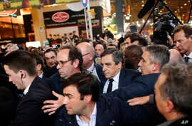 Conservative presidential candidate Francois Fillon, center right, makes his way while visiting the Agriculture Fair in Paris, March 1, 2017. Fillon is refusing to quit the race despite receiving a summons Wednesday to face charges for alleged fake p