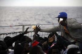 Migrants share slices of bread on the deck of the Belgian Navy vessel Godetia after they were saved at sea during a search and rescue mission in the Mediterranean Sea off the Libyan coasts, June 24, 2015