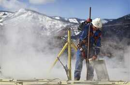 Worker checks water levels, temperatures in a series of tanks at an Encana Oil & Gas (USA) Inc. hydraulic fracturing operation at a gas drilling site outside Rifle, Colorado, March 29, 2013.