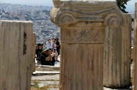 FILE - Tourists take photographs atop of the ancient Acropolis hill in Athens, May 9, 2016. Greece expects to welcome a record 27 million tourists this year.