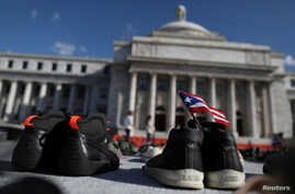 FILE - A Puerto Rican flag is seen on a pair of shoes as hundreds of pairs of shoes are displayed at the Capitol to pay tribute to Hurricane Maria's victims, in San Juan, Puerto Rico June 1, 2018.