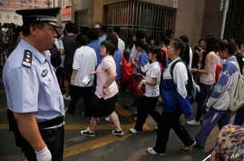 FILE - Chinese students walk past a police officer on their way to the annual college entrance examinations held in Beijing, China.