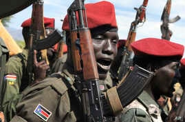 FILE - Government soldiers follow orders to raise their guns during a military parade in Juba, South Sudan, April 14, 2016.