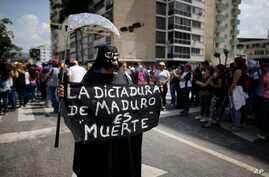 "A woman dressed in a grim reaper costume holds a sign that reads in Spanish: ""Maduro's dictatorship is death"" during a rally in Caracas, Venezuela, April 27, 2017."