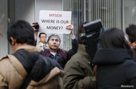 Kolin Burges, a self-styled cryptocurrency trader and former software engineer from London, holds up a placard to protest against Mt. Gox, in front of the building where the digital marketplace operator was formerly housed in Tokyo, Japan, Feb. 26, 2