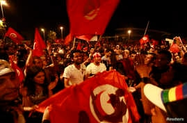 Anti-government protesters wave national flags during a demonstration in Tunis, August 6, 2013.