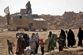Civilians fleeing the battered Islamic State-held holdout of Baghuz walk past an armored vehicle belonging to the Manbij military council into a nearby area held by the Syrian Democratic Forces (SDF) in Syria, Feb. 12, 2019.