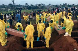 Volunteers handle a coffin during a mass funeral for victims of heavy flooding and mudslides in Regent at a cemetery in Freetown, Sierra Leone, Aug. 17, 2017.