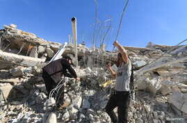 People look for survivors in the ruins of a destroyed Medecins Sans Frontieres (MSF) supported hospital hit by missiles in Marat Numan, Idlib province, Syria, February 16, 2016.