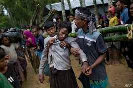 Kifawet Ullah is helped by other newly arrived Rohingya after he collapsed while waiting to have his token validated in order to collect a bag of rice distributed by aid agencies in Kutupalong, Bangladesh, Sept. 9, 2017.