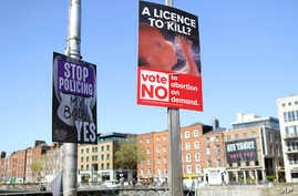 FILE - In this photo taken May 17, 2018, pro and anti-abortion poster's on lampposts, in Dublin. In homes and pubs, on leaflets and lampposts, debate rages in Ireland over whether to lift the country's decades-old ban on abortion.