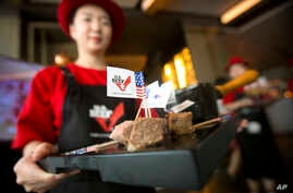 A hostess holds a tray of sliced American beef at an event to celebrate the re-introduction of American beef imports to China in Beijing, June 30, 2017.