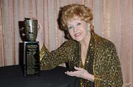 "FILE - Debbie Reynolds, shown with her SAG Lifetime Achievement Award in January 2015, rose to fame in 1952's ""Singin' in the Rain"" and earned an Oscar nomination for 1964's ""The Unsinkable Molly Brown."""