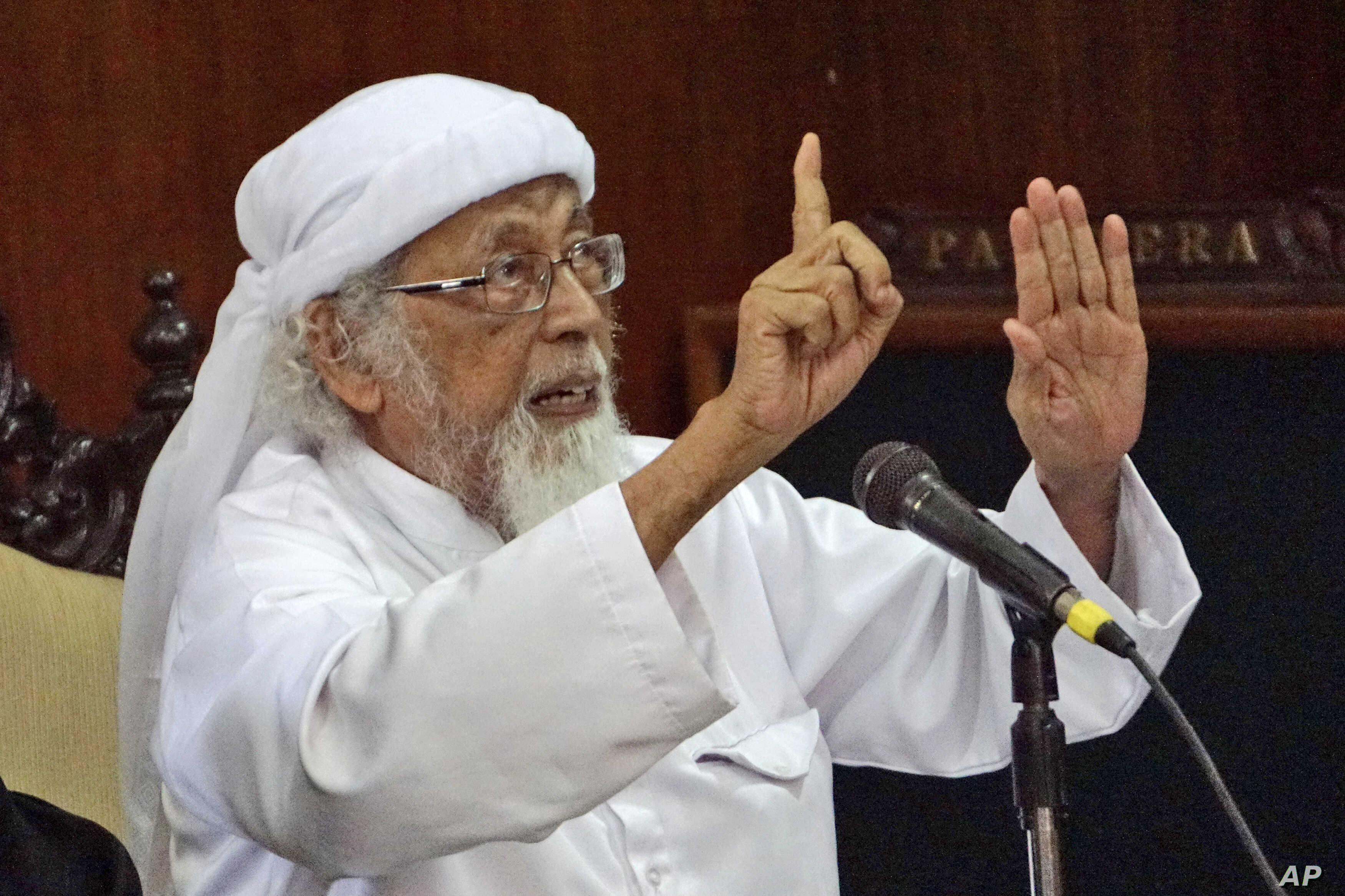 FILE - Radical Islamic cleric Abu Bakar Bashir gestures as he speaks to the judges during his appeal hearing at the district court in Cilacap, Central Java, Indonesia, Feb. 9, 2016. The 77-year-old cleric who was sentenced to 15 years in jail in 2011