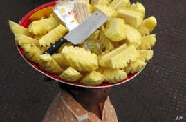 A vendor carries pieces of pineapple on her head during business at a jetty in Yangon, Myanmar, June 4, 2011.