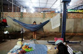 Venezuelan women are pictured near their improvised beds during the night at the car repair shop, near the interstate Bus Station in Boa Vista, Roraima state, Brazil, Aug. 24, 2018.