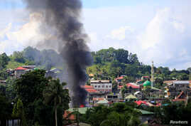 Smoke billowing from a burning building is seen as government troops continue their assault on insurgents from the Maute group, who have taken over large parts of Marawi City, Philippines, June 1, 2017.