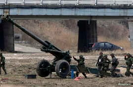 """South Korean soldiers of an artillery unit take part in an artillery drill with 155mm Towed Howitzers as part of the annual joint military exercise """"Foal Eagle"""" by the U.S. and South Korea, near the demilitarized zone (DMZ) which separates the two Ko"""