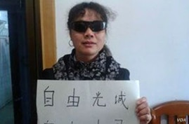 Jiangxi-based activist Liu Ping holds a sign expressing solidarity with blind civil rights lawyer Chen Guangcheng.