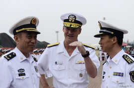 Robert L. Thomas Jr. (C),  Commander of the U.S. Seventh Fleet talks with Chinese general Yuan Yubo (L) at a port in Qingdao, during the U.S. Seventh Fleet Flagship USS Blue Ridge (LCC 19) visit to China, Shandong province, August 5, 2014.