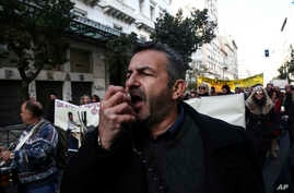 A protester chants slogans during a rally by health workers in Athens, Dec. 14, 2016. Workers in the country's health sector marched through the streets of the Greek capital to protest against government's planned reforms, which will affect their sec