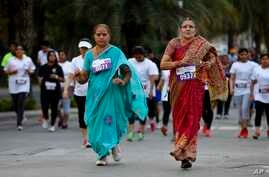 Middle aged women in traditional Indian attire run along with youngsters during a 5 Kilometer run, organized to celebrate International Women's Day in Bangalore, India, Sunday, March 8, 2015.