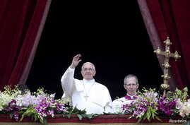 """Pope Francis waves as he delivers a """"Urbi et Orbi"""" message from the balcony overlooking St. Peter's Square at the Vatican, April 5, 2015."""