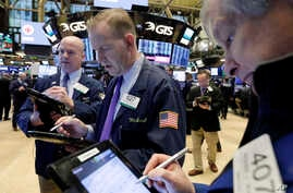Traders Patrick Casey, left, Michael Smyth, center, and Richard Newman work on the floor of the New York Stock Exchange, Feb. 7, 2018.