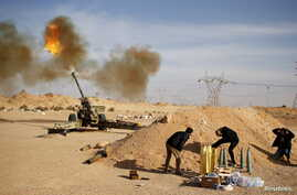 FILE - Libya Dawn fighters fire an artillery cannon at Islamic State militants near Sirte, March 19, 2015.