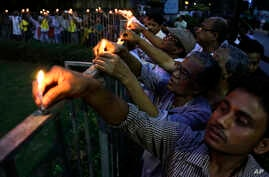 Indian people put candles onto fence as they protest killing of Avijit Roy, a prominent Bangladeshi-American blogger, in Kolkata, India, March 1, 2015.