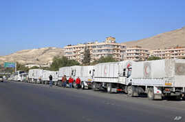 FILE - A convoy of humanitarian aid waits in front of the United Nations Relief and Works Agency (UNRWA) offices before making their way into the government besieged rebel-held towns of Madaya, al-Zabadani and al-Moadhamiya in the Damascus countrysid