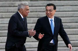 Sri Lanka's Prime Minister Ranil Wickremesinghe, left, chats with Chinese Premier Li Keqiang during a welcome ceremony outside the Great Hall of the People in Beijing, April 7, 2016.
