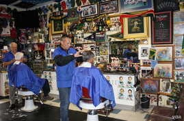 Bennie Botes (far left) and Louis de Hart at work inside their barbershop in Newlands, Johannesburg. The wall holds just a fraction of the rugby memorabilia collected by Botes over the past 50 years. (Darren Taylor for VOA News)