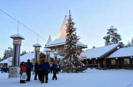 Visitors walk in Santa Claus Village, around 8 kilometers (5 miles) north of Rovaniemi, Finland, Dec. 15, 2015. Most kids learn Santa Claus comes from the North Pole. But where exactly is a matter of much debate in Finland, Sweden and Norway.