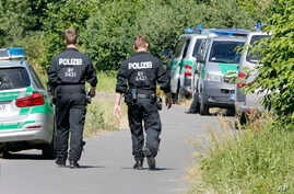 Police officers walk to  the crime scene near the river Main, background, where a 17-year-old man from Afghanistan was shot the night before, in Wuerzburg, Germany, Tuesday, July 19, 2016.