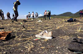 People walk past a part of the wreckage at the scene of the Ethiopian Airlines Flight ET 302 plane crash, near the town of Bishoftu, southeast of Addis Ababa, March 10, 2019.