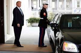 President Donald Trump stands in the entrance of the the West Wing of the White House in Washington, Feb. 15, 2017, with a limousine standing in the portico.
